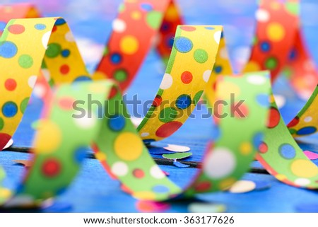 colorful paper streamer at carnival party over blue background - stock photo