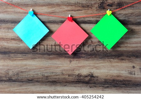 Colorful paper with clothespin hanging on a string with wooden background, retro style. - stock photo