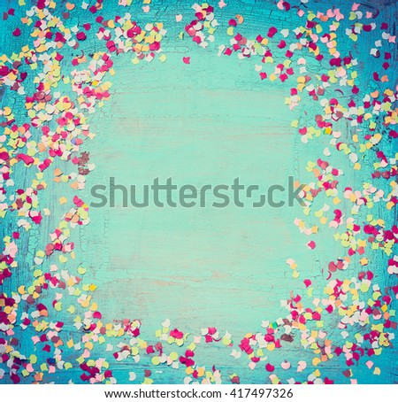 Colorful party confetti on turquoise shabby chic background, top view, place for text, frame. Festive greeting card. Party background. - stock photo