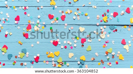Colorful party confetti, some heart-shaped, on a rustic blue wood background scattered randomly across the surface, wide angle view - stock photo