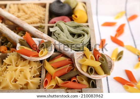 Colorful pasta in wooden box on wooden table background