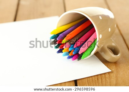 Colorful pastel crayons with sheet of paper on wooden table, closeup - stock photo