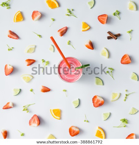 Colorful pattern made of citrus fruits, leaves and strawberries with smoothie. - stock photo