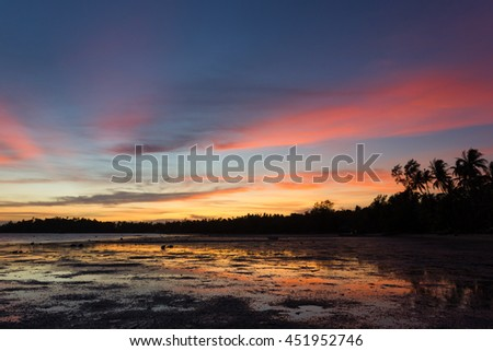 Colorful, peaceful sunset landscape on the beach in the island of Koh Phangan, Thailand. The colors of the sky reflect on shallow water in low tide. - stock photo