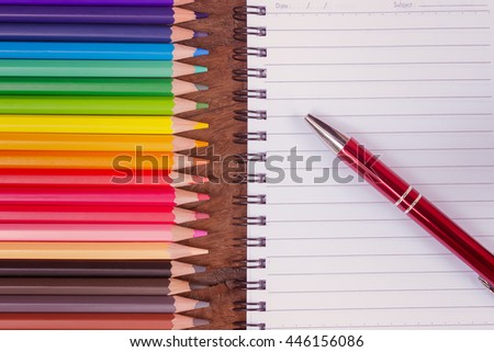 colorful pencil crayons and blank notebook  on wood background,Pen