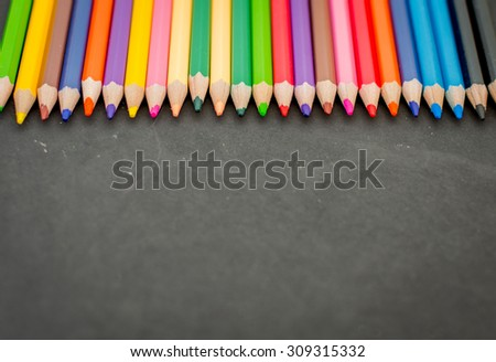 Colorful pencil crayons on a blackboard background - stock photo