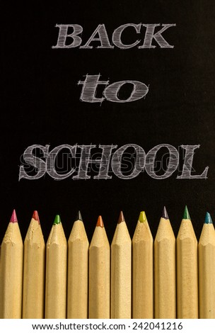 Colorful pencil crayons over a blackboard background, Back to school - stock photo