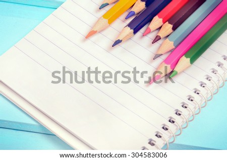 Colorful pencil with notepad on blue wooden table