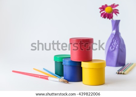 colorful pencils and paintbrushes with liquid paint containers on foreground and flower in vase on white background  - stock photo