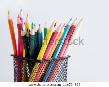 colorful pencils in a holder on a white background close-up