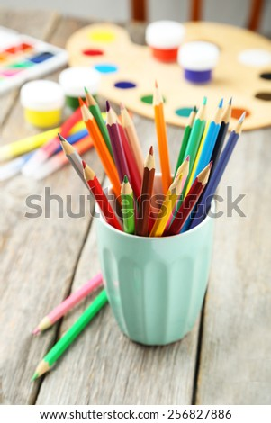 Colorful pencils in cup on grey wooden background - stock photo