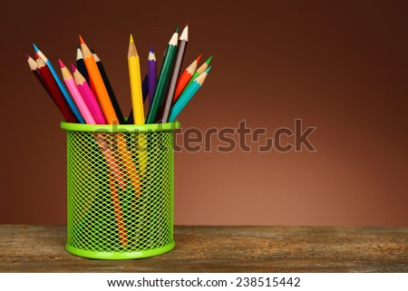 Colorful pencils in green metal holder on wooden table and shaded color background