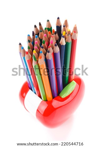 Colorful pencils in red apple shaped stand isolated on white - stock photo