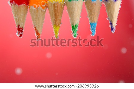 Colorful pencils in water with bubbles on red background - stock photo