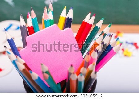 Colorful pencils of red yellow orange violet purple pink green and blue and stick on school desk with white sheet of paper on written with chalk blackboard background copyspace, horizontal picture - stock photo