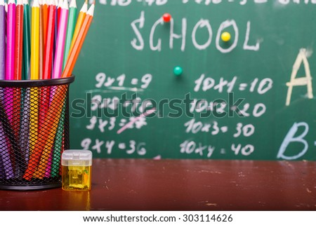 Colorful pencils of red yellow orange violet purple pink green and blue in stationary cup and steel standing on brown school desk on written with white chalk blackboard backgroung on lesson of math - stock photo