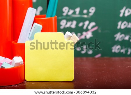 Colorful pencils of red yellow orange violet purple pink green and blue in stationary cup and stick on brown school desk on written with white chalk blackboard background copyspace, horizontal picture - stock photo