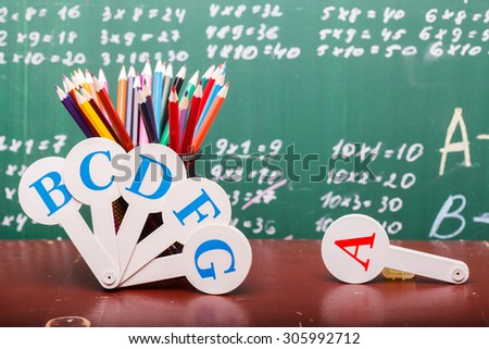 Colorful pencils of red yellow orange violet purple pink green and blue in stationary cup ruler and fan english alphabet standing on brown school desk on written with white chalk blackboard on math - stock photo