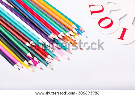 Colorful pencils of red yellow orange violet purple pink green blue chalk and fan english alphabet with capital letters lying on white school desk background copyspace, horizontal photo - stock photo