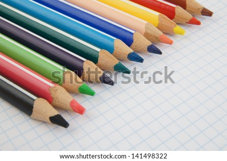 Colorful pencils on checked note paper - stock photo