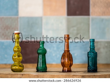 Colorful perfume phials in front of colorful handmade ceramic tiles