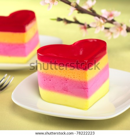 Colorful Peruvian heart-shaped jelly-pudding cakes called Torta Helada with a blooming peach branch in the back (Selective Focus, Focus on the front of the first cake)