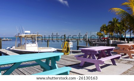 Colorful picnic tables line the boardwalk of this Fiesta Key marina - stock photo