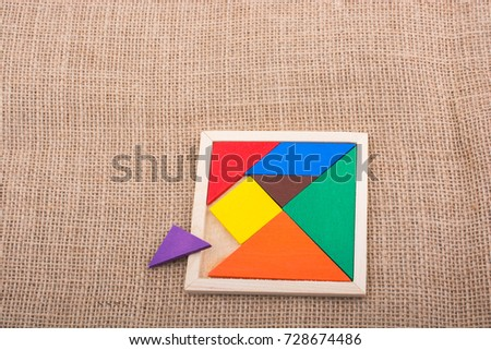 Colorful pieces of a square tangram puzzle
