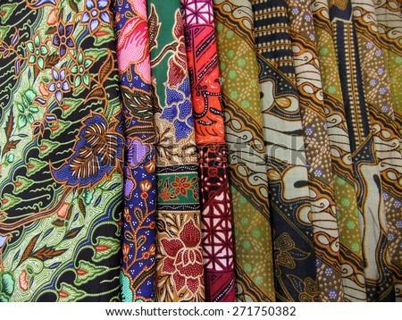 Colorful pile of batik fabrics or textiles - stock photo