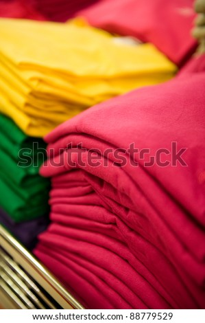 Colorful pile of T-shirts in a shop.