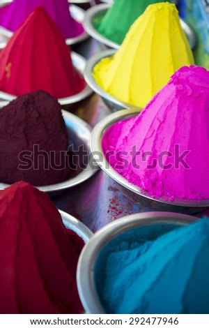 Colorful piles of Indian bindi powder dye at outdoor local Devaraja Market in Mysore India feature blue, yellow, red, green, pink, and purple