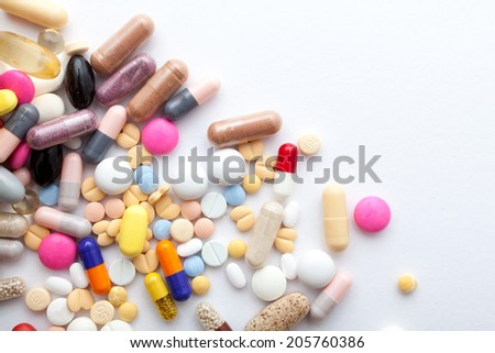 Colorful pills and  capsules on white - stock photo