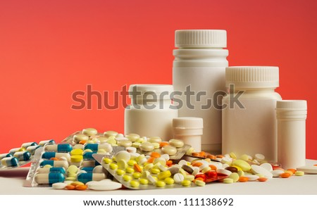Colorful pills, capsules, dragee and white bottles - stock photo
