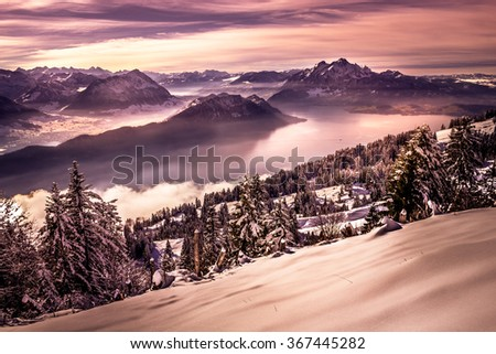 Colorful pink sunset with view on distant mountains and valley with a lake and forest covered by snow in the cold winter - stock photo