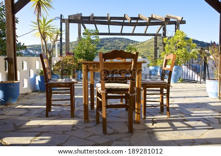 Colorful plants, tables and chairs in a tavern early in the morning in the mountain village Pitsidia in south Crete.