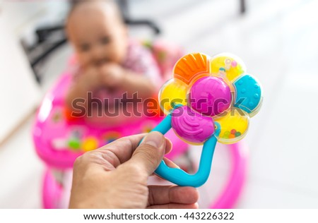 colorful plastic baby toy and blurry baby in car walker in background - stock photo