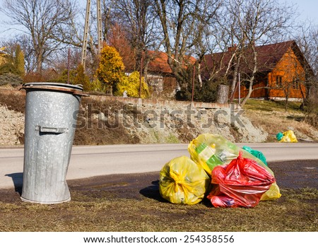 Colorful plastic bags and metal rubbish bin by street in small polish country  - stock photo