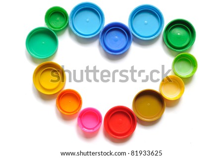 Colorful plastic bottle screw caps used to seal plastic bottles, arranged in heart shape - stock photo