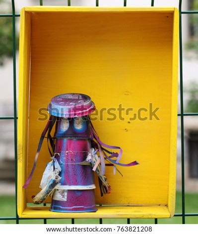 Colorful plastic creature in a yellow wooden box