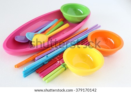 Colorful plastic cutlery, round bowl and chopsticks. - stock photo