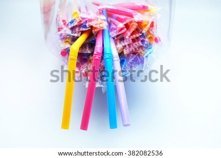 Colorful plastic drinking straws in plastic wraps with transparent bowl on blue-white background. Focus on extended straws. Space for texts. - stock photo
