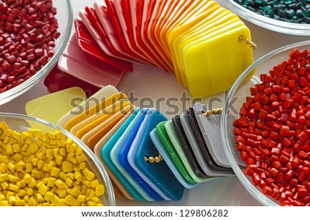 Colorful plastic granules and finished plastic plates - stock photo