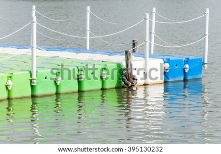 Colorful plastic pontoon with rubber surface is floating on the tranquil lake. - stock photo