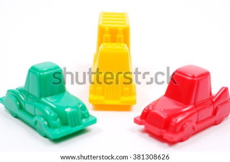 Colorful plastic toy cars of different colors on a white background. Passenger cars blocked the truck. Close up view, selective focus. - stock photo