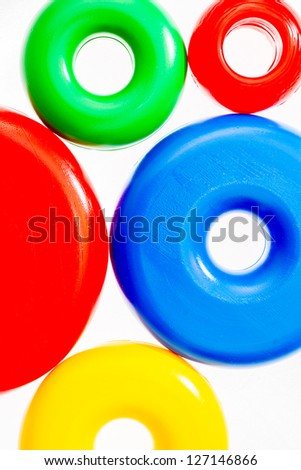 Colorful plastic toy rings on white background - stock photo
