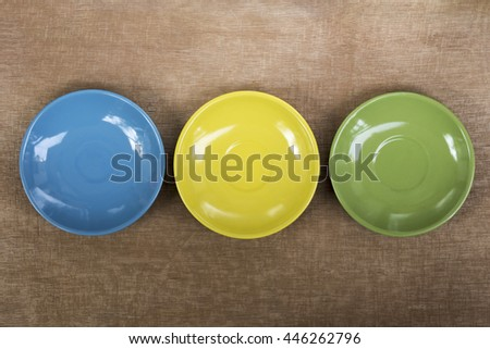Colorful plates and saucers over wooden table background. View from above - stock photo