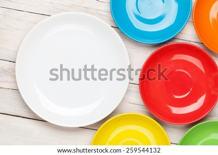 Colorful plates over white wooden table background with copy space - stock photo