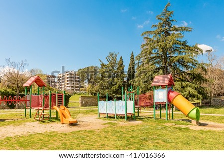 Colorful playground for kids inside a urban public park in Italy - stock photo