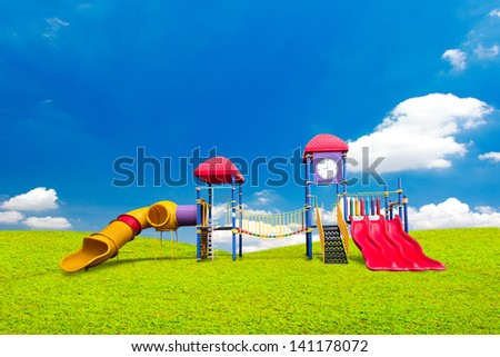 colorful playground on green grass and blue sky background - stock photo