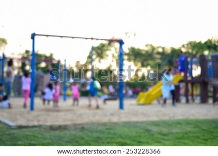 Colorful playground with children and parents in park (blur background) - stock photo